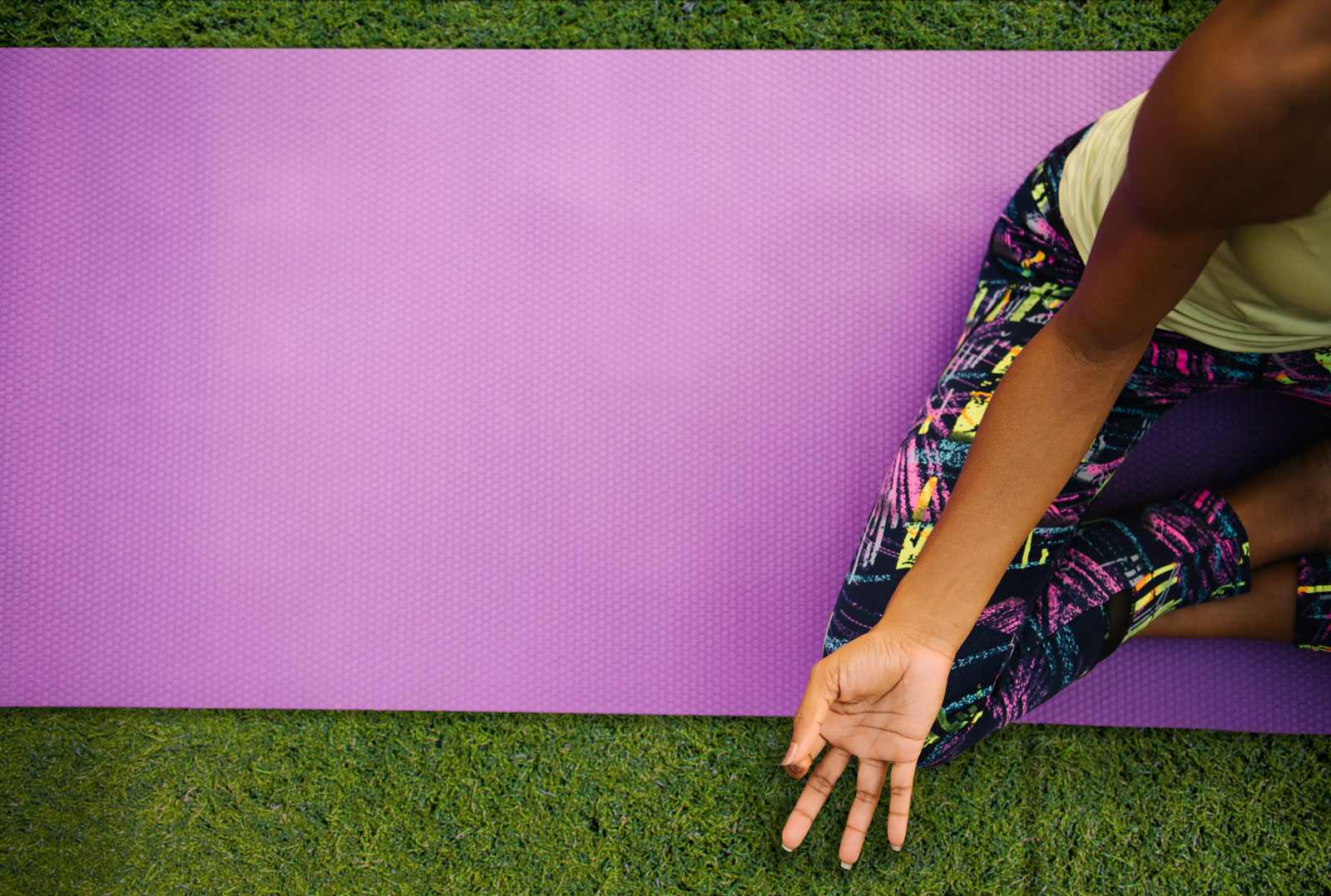 a woman doing yoga in a purple mat on the grass